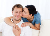 Lovely woman kissing her boyfriend while relaxing on the sofa — Stock Photo