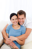 Portrait of a happy man hugging his girlfriend while relaxing on — Stock Photo