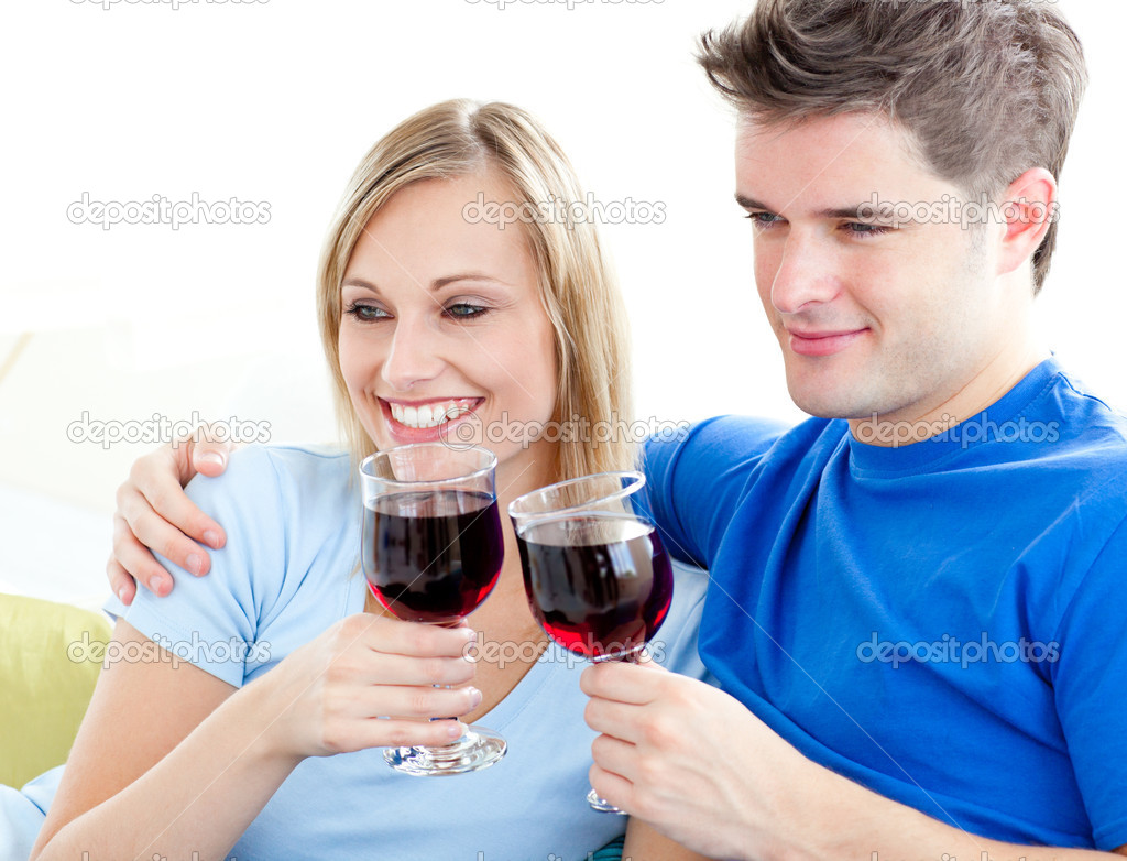 Affectionate couple drinking wine sitting on a sofa in the living room — Stock Photo #10830037
