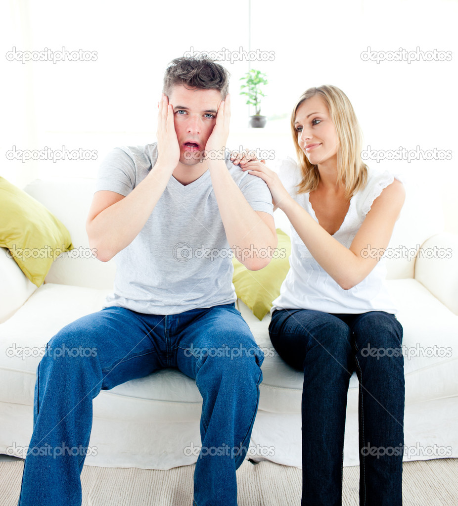 Shocked man sitting on the sofa with his girlfriend at home — Stock Photo #10830045
