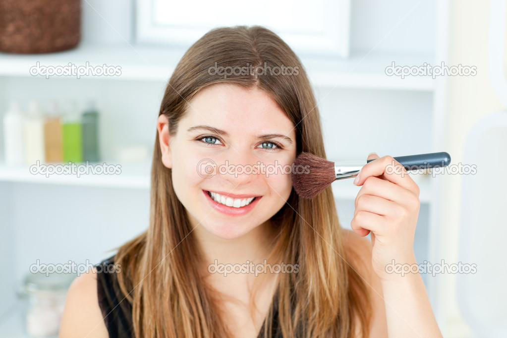 Smiling caucasian woman putting powder on her face smiling at the camera in the bathroom — Stok fotoğraf #10830822