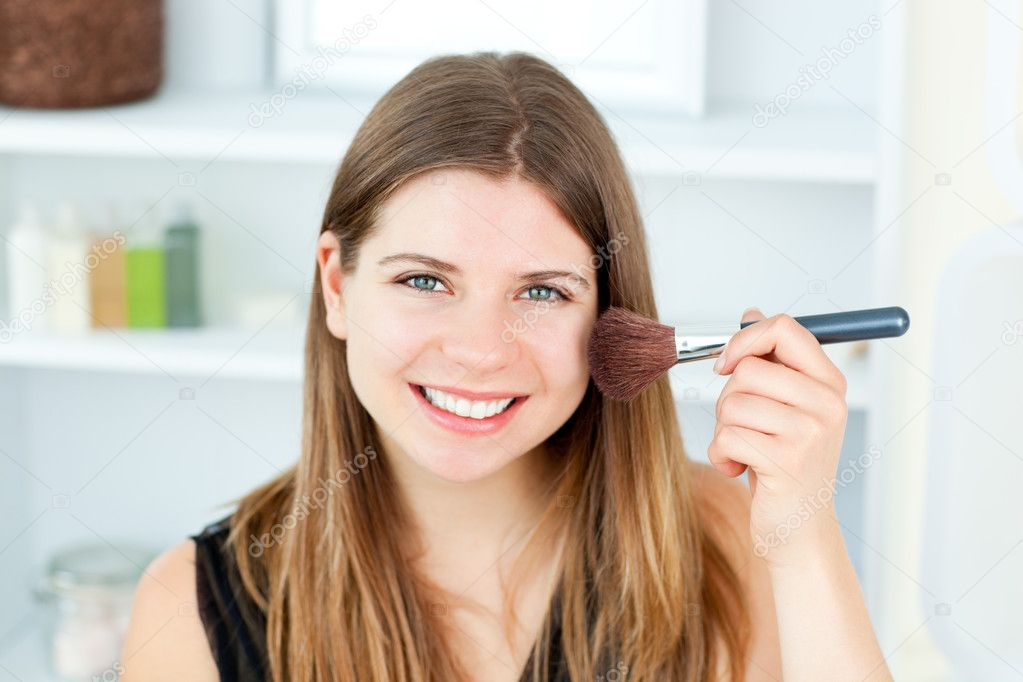 Smiling caucasian woman putting powder on her face smiling at the camera in the bathroom — Stockfoto #10830822