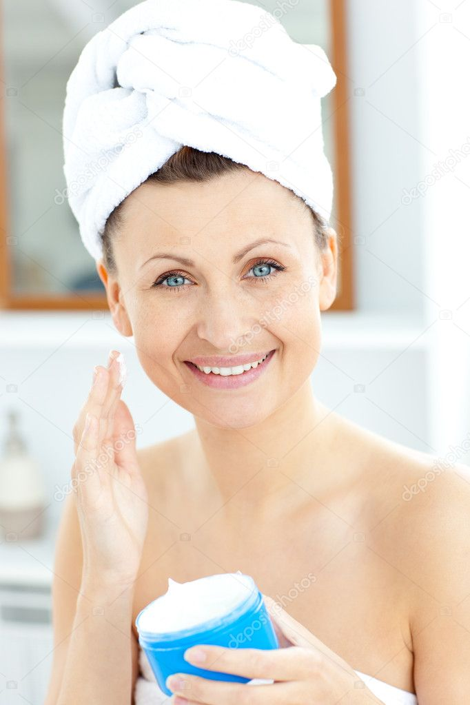 Pretty young woman putting moisturizer on her face looking at the camera in the bathroom — Stock Photo #10830967