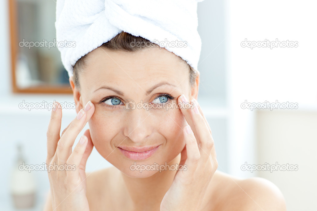 Smiling young woman putting moisturizer on her face  in the bathroom — Stock Photo #10830970