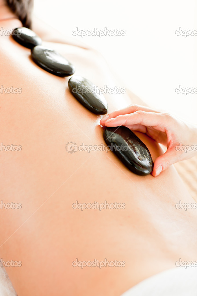 Close-up of a man receiving hot stone on his back in a beauty treatment — Stock Photo #10831504