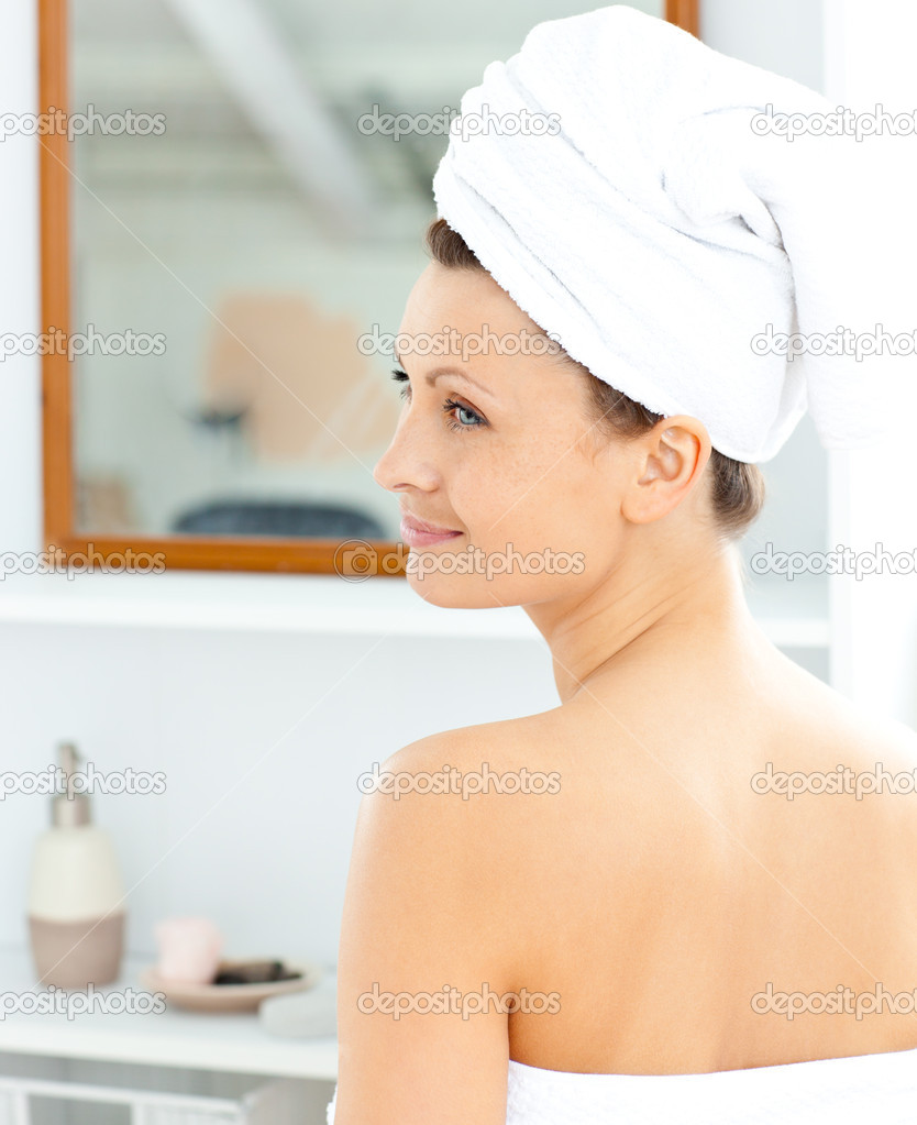 Positive young woman with a towel putting cream on her face in the bathroom at home — Stock Photo #10832666