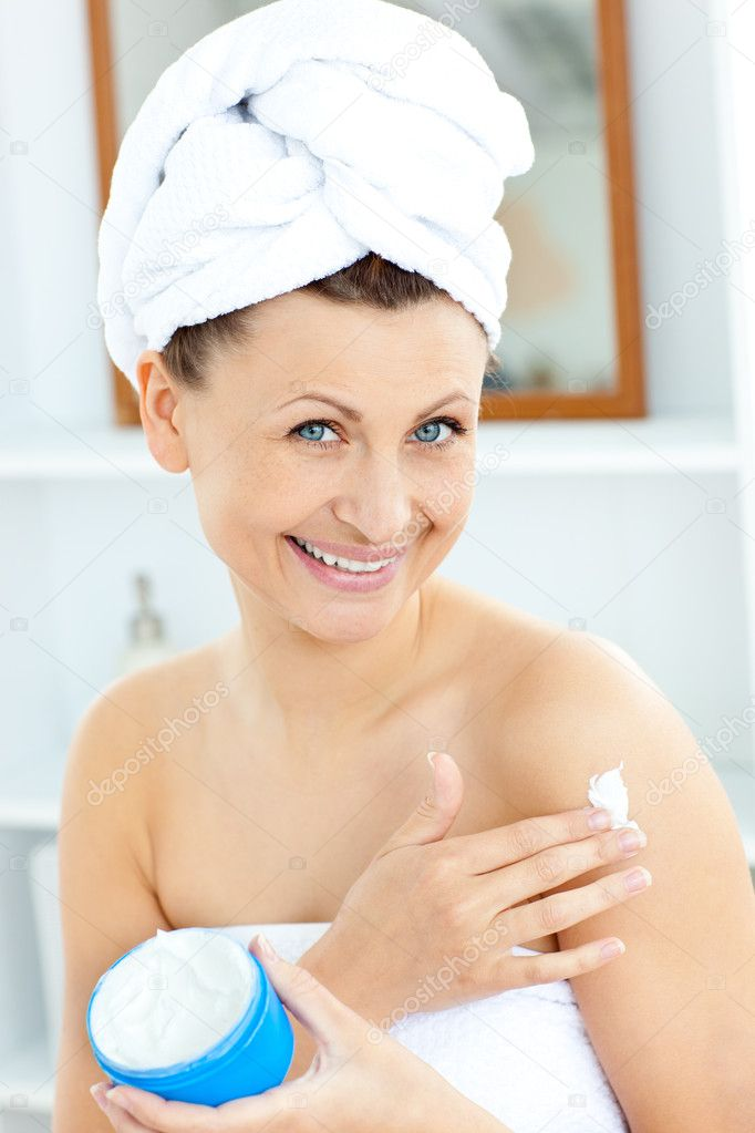 Charming young woman with a towel putting cream on her face in the bathroom at home — Stock Photo #10832669
