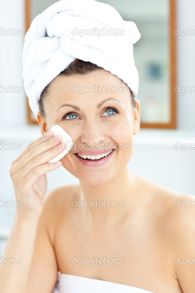 Smiling young woman with a towel putting cream on her face in the bathroom at home — Stock Photo #10832673