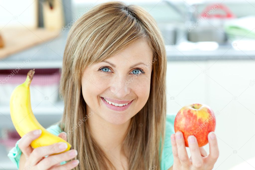 Positive caucasian woman holing a banana and an apple in the kitchen at home — Stock Photo #10832805