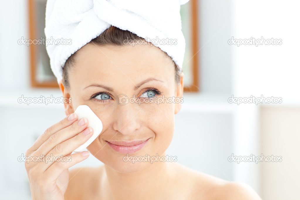 Young woman putting cream on her face wearing a towel in the bathroom at home — Stok fotoğraf #10833826