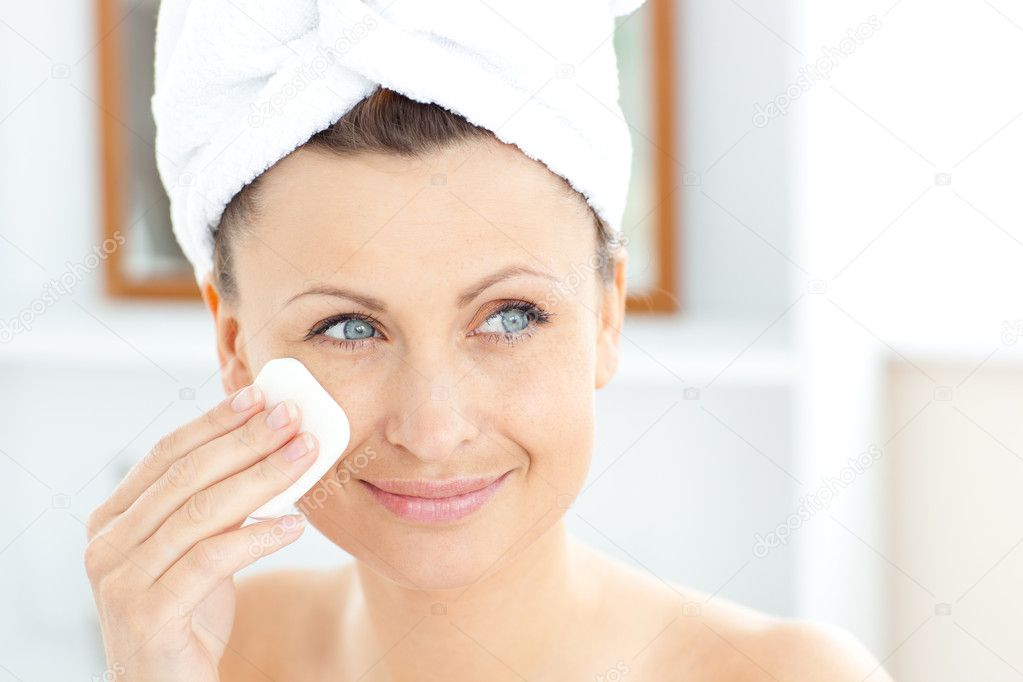 Young woman putting cream on her face wearing a towel in the bathroom at home — ストック写真 #10833826