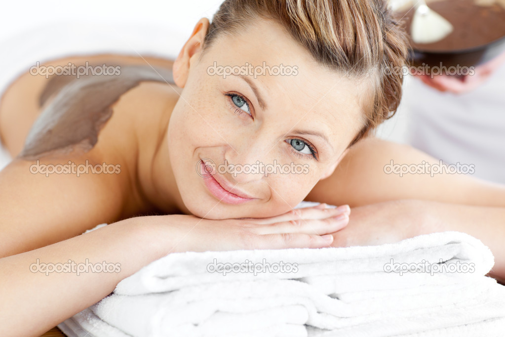 Portrait of a radiant woman lying on a massage table with mud on her back in a spa center — Stock Photo #10834667