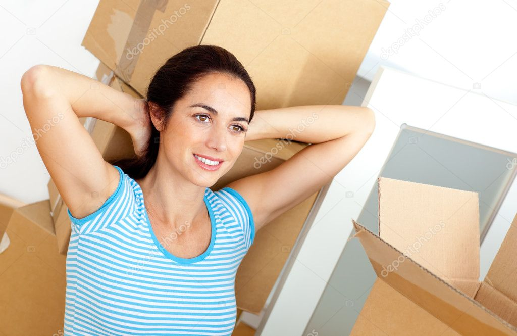 Relaxed young woman sitting on the floor after unpacking cardboards in her new house — Stock Photo #10835174