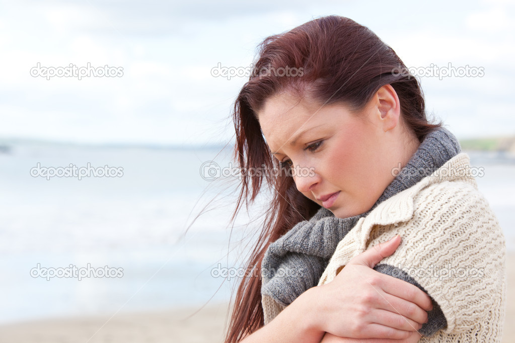 Unhappy woman wearing sweater on the beach and getting cold — Photo #10835254