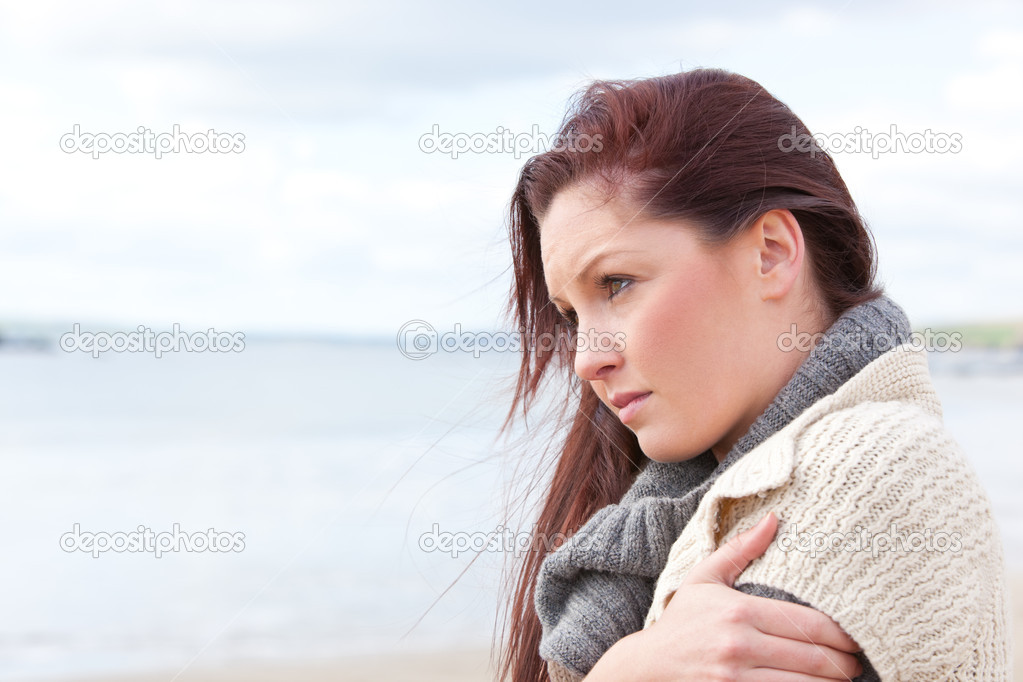 Unhappy woman wearing sweater on the beach and getting cold — Stock Photo #10835256