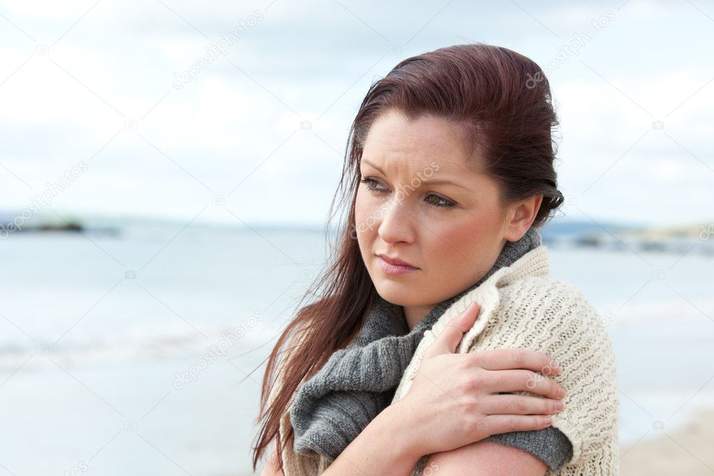 Unhappy woman wearing sweater on the beach and getting cold — Stock Photo #10835260