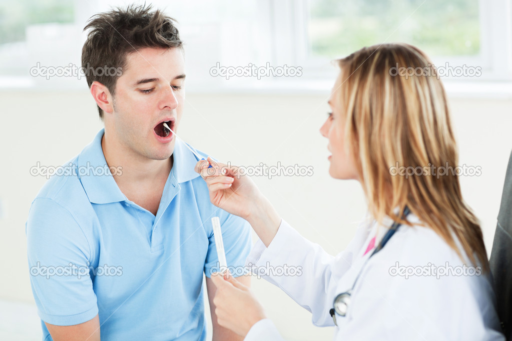 Female doctor extracting saliva from the mouth of her patient — Stock Photo #10835520