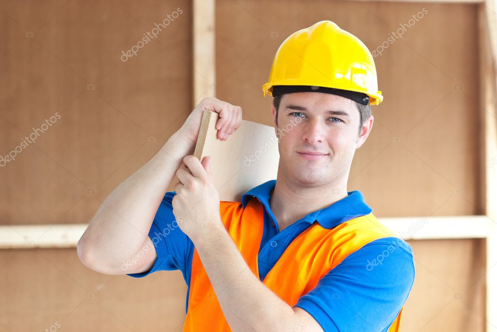 Confident young male worker with a yellow helmet carrying a wooden board at work — Stock Photo #10836580