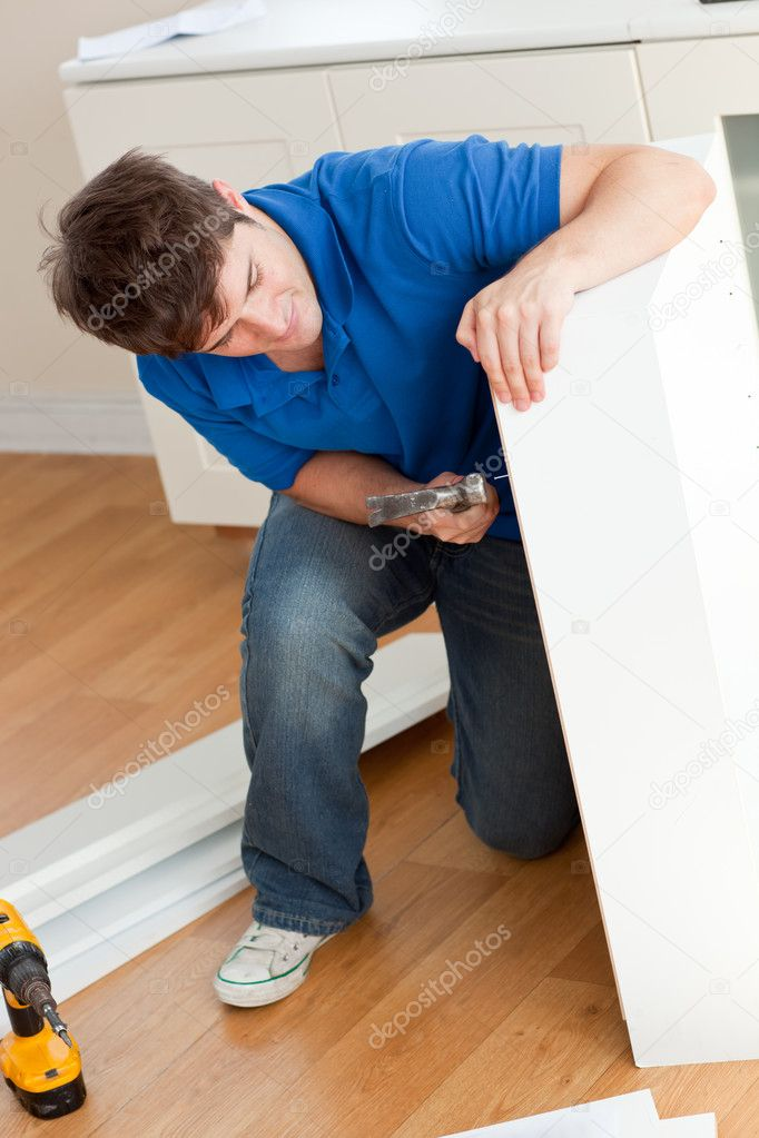 Good-looking man assembling furniture and holding a hammer at home — Stock Photo #10836660