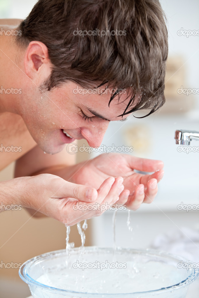 Smiling caucasian man spraying water on his face after shaving in the bathroom at home  Stock Photo #10836765
