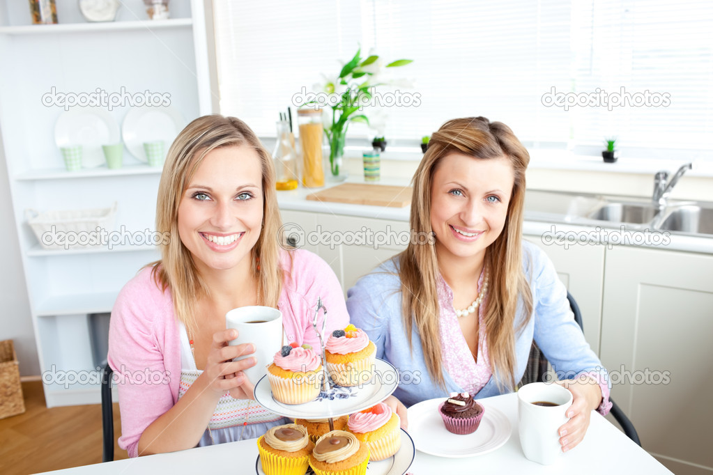 Portrait of two attractive women with cups of coffee and cupcakes sitting in the kitchen at home — Stock Photo #10837576
