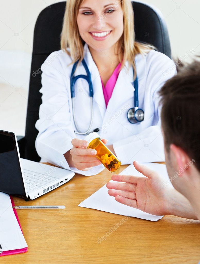 Portrait of an attractive doctor giving pills to her patient during an appointment in her office — Stockfoto #10837938