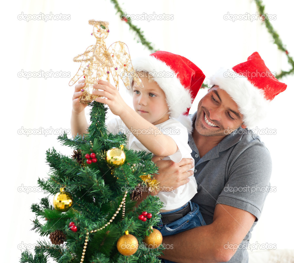 Happy father helping his son to put an angel on the Christmas tree at home — Foto Stock #10838617