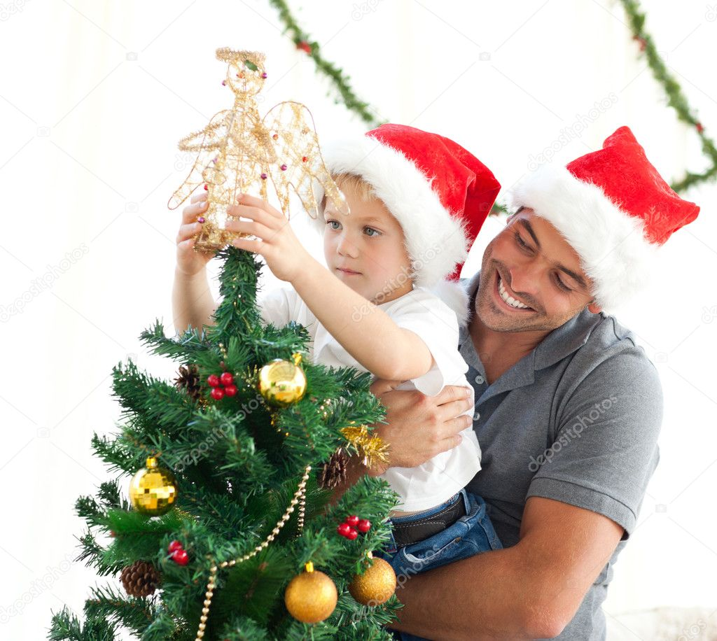 Happy father helping his son to put an angel on the Christmas tree at home — Lizenzfreies Foto #10838617