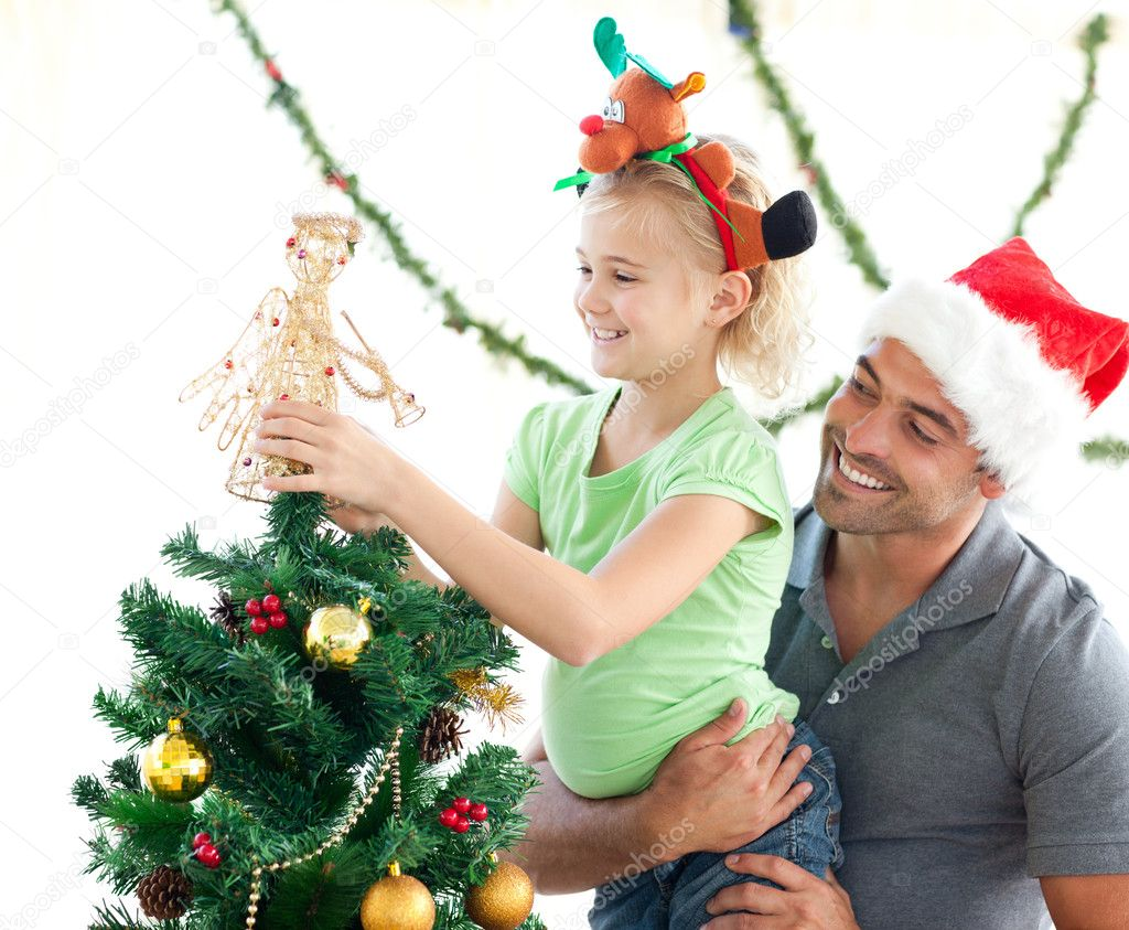 Cute little girl decorating the christmas tree with her father at home  Foto Stock #10838626