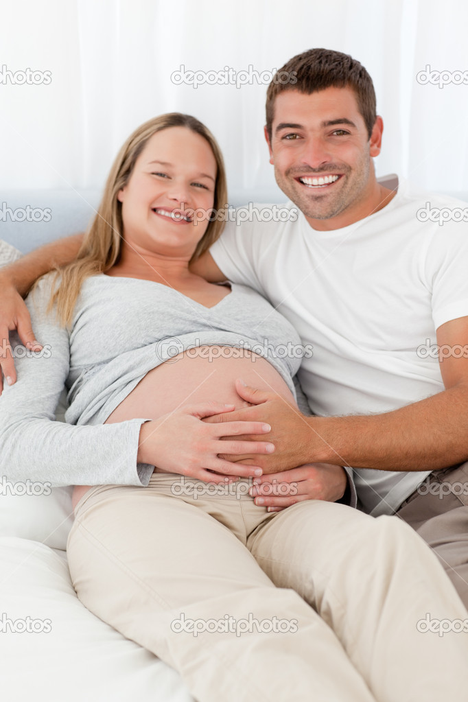Happy future parents lying on a bed and looking at the camera — Stock Photo #10838792