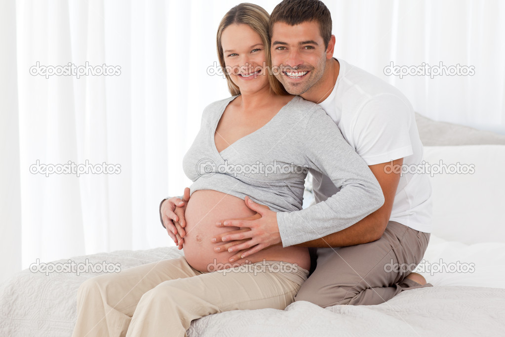 Pregnant woman touching her belly with her husband both sitting in the bedroom — Stock Photo #10838843
