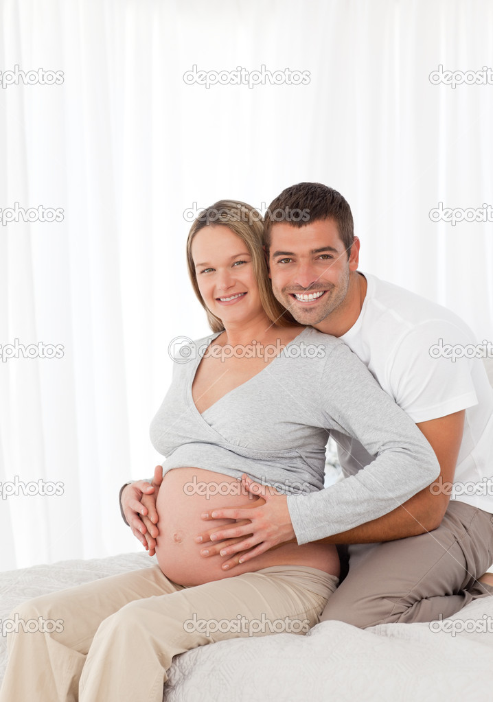 Cute pregnant woman touching her belly with her husband in the bedroom at home — Stock Photo #10838844