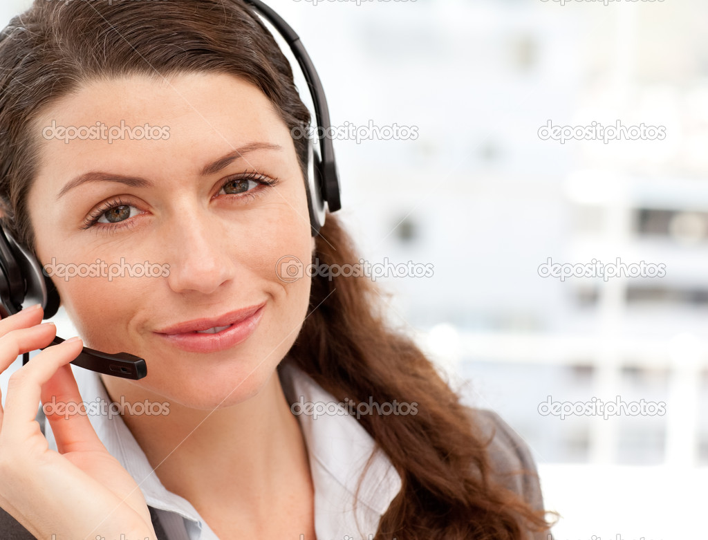 Pretty businesswoman with earpiece smiling at the camera in an office — Stock Photo #10838958