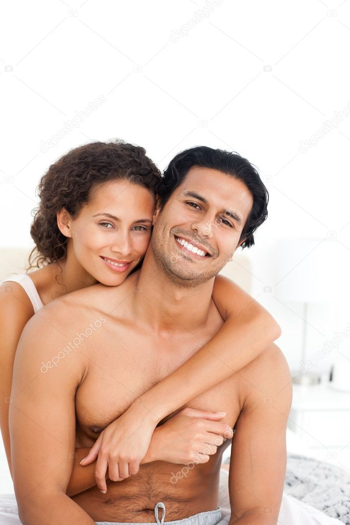 Portrait of a woman hugging her husband sitting together in the bedroom  Stock Photo #10839334