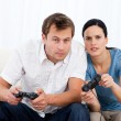 Concentrated couple playing video games together on the sofa - Stock Photo