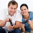 Joyful couple playing video games together on the sofa — Stock Photo #10840042