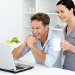 Happy couple looking at something on the laptop while drinking c — Stock Photo
