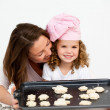 Happy little girl with her mother showing a plate with biscuits — Stock Photo