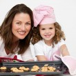 Stock Photo: Lovely mother and daughter holding a plate with biscuits