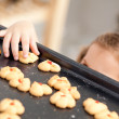 Close up of a little girl taking a cookie behind her mother's ba — Stock Photo