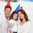 Portrait of cute little girl with her parents during a birthday — Stock Photo