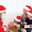 Santa giving presents to his children in the living room — Stock Photo #10840345