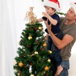 Cute son decorating the christmas tree with his father — Photo
