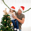 Cute daughter decorating the christmas tree with his father - Foto Stock