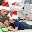Stock Photo: Father and son unwrapping present lying on floor