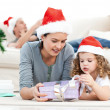 Mother and daughter unwrapping present lying on floor — Stock Photo #10840369