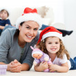 Happy mother and daugher at christmas lying on the floor - Foto Stock