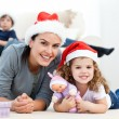 Happy mother and daugher at christmas lying on the floor - Stockfoto
