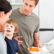 Little boy giving his mother a carrot while preparing lunch — Stock Photo