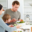 Dad serving salad to his family for lunch - Stock Photo